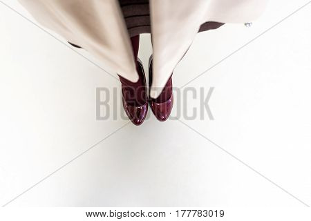 Top view of lower part of woman's body with clothes and vinous high-heeled shoes on