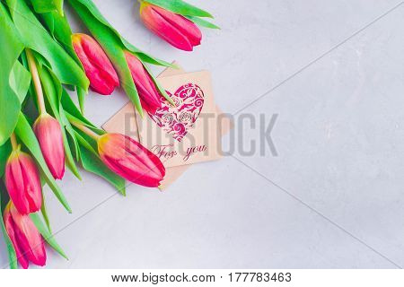 Spring Flowers holiday Background. Easter or Mother Day Gift Present. Pink tulips on gray light table with paper card For You. Copy space top view place for text