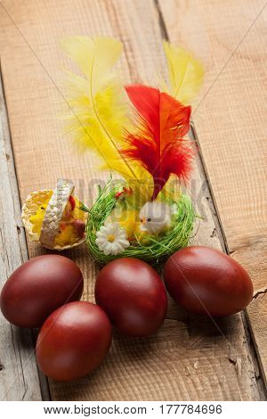 Red Easter Eggs On Old Wood Table With Feather And Chicken