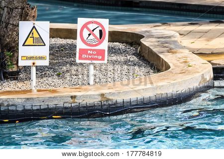 Closeup of no diving and depth signs in swimming pool