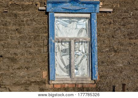 Close up of obsolete weathered wooden window in stone wall