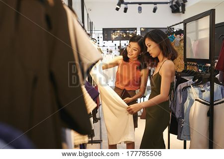Beautiful fashionable women choosing clothes in boutique