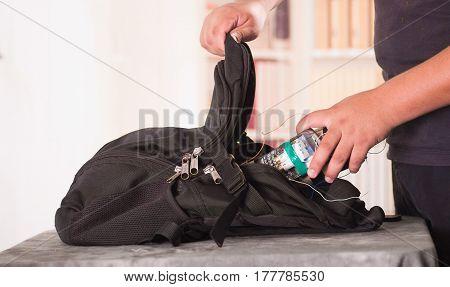 Close up shot of hands putting an improvised explosive device bomb inside black backpack