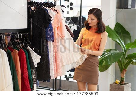 Pretty Vietnamese young woman looking at summer dress in fashion boutique
