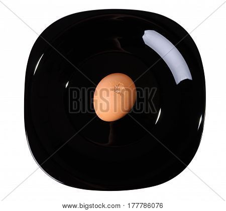 Cracked egg on a black plate isolated on the white