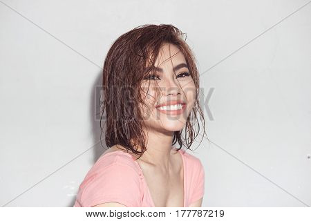 Fresh summer look. Beautiful young asian model with wet hair golden makeup tanned skin.