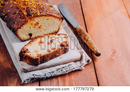 Citrus cake with dried fruits for breakfast or teatime on Grate for cooling on stone table background. Copy space vertical horizontal image