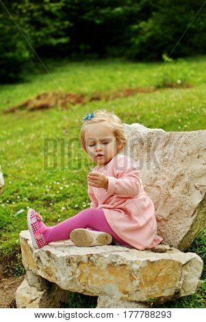 Little Girl Sitting On A Throne Of Stone