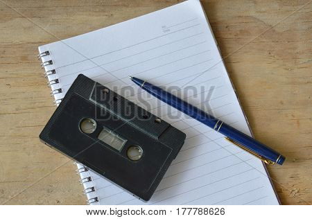 audio cassette tape recorder and blue pen on book