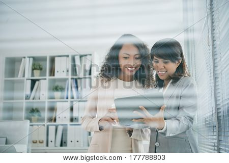 Smiling Asian business women reading data on screen of digital tablet