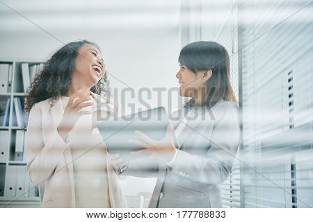 Business ladies with digital tablet in hands laughing