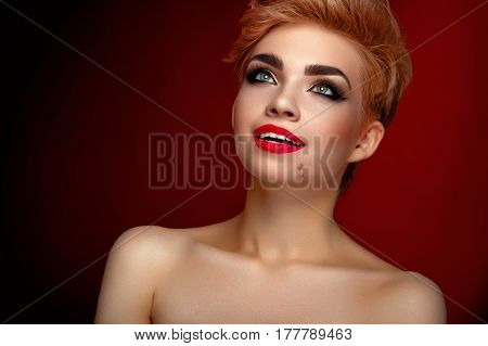 Red lips are always in trend. Young beautiful cheerful woman smiling looking away wearing professional makeup with red lips and dark smoky eyes copyspace happiness smile smiling eye shadow lipstick