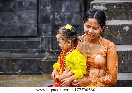 PURA BESAKIH, INDONESIA - SEPTEMBER 30, 2012: Mother and daughter in Pura Besakih Temple in Bali Island Indonesia