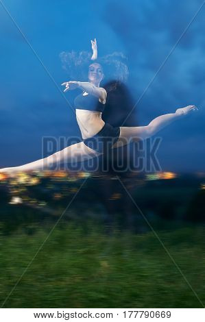 pretty, young, smiling dancer performs splits in the air at the grassy field in front of the night lights of the city.