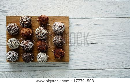 Healthy raw energy balls with cocoa coconut sesame chia on a white textured wooden background. Vegan chocolate truffles. Copy space