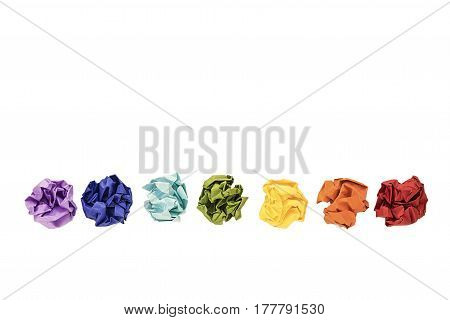 Crumpled colorful paper balls isolated on white. Colors of rainbow chakras. Copy space