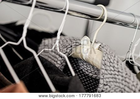 Designer clothing hang on a rack. Knit grey cardigan