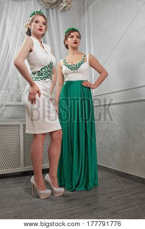 two young, beautiful woman, brunette, blonde in white short dress and long green dress, on heels, hands on hips, in the room.