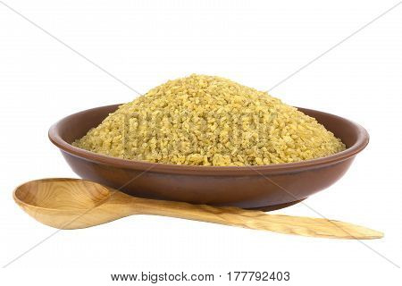 Dry bulgur wheat in a clay bowl isolated on white with spoon