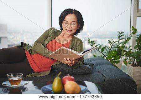 Senior Asian woman lying on sofa and reading a book