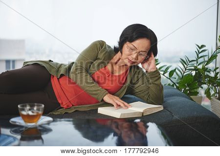Aged Vietnamese woman with a book lying on couch