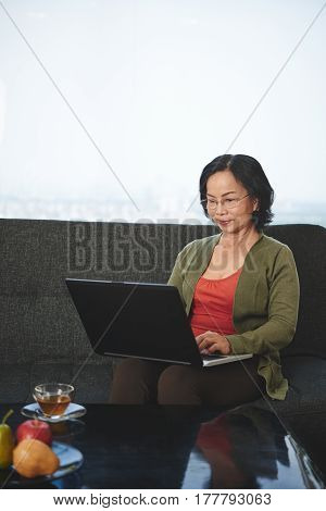 Pretty senior woman sitting on sofa and working on laptop