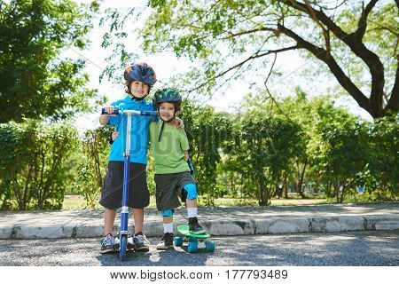 Cheerful little brothers with kick scooter and skateboard