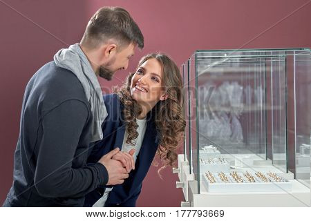 Shopping with her significant other. Beautiful happy young woman smiling cheerfully looking at her man after choosing an engagement ring at the jewelry store