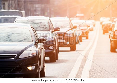 Zoom view of the road with grey cars in the rush hour against the sunlight