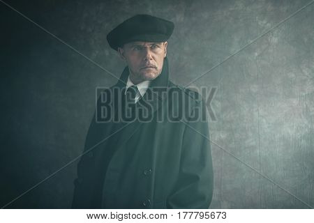 Retro 1920S English Gangster Wearing Flat Cap And Coat.