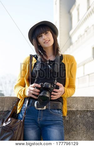 Portrait of a young and attractive woman taking a photo outdoor