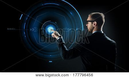 business, future technology, cyberspace and people - businessman in suit and glasses pointing finger to virtual projection over black background