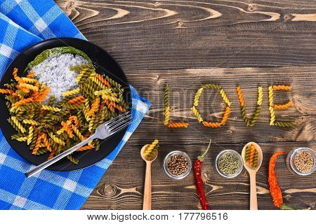 Love word from dried fusilli for valentines day on brown wooden background. Italian pasta in black plate on blue plaid tablecloth peppers salt spices ingredients for cooking with fork and spoons