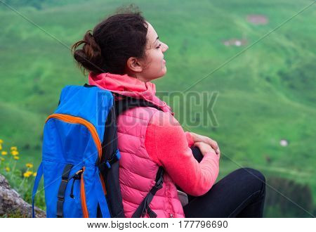 Woman Hiker With Backpack Relaxing On Top Of A Mountain And Looking At Mountains
