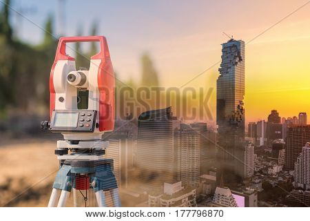 Double exposure surveyor equipment theodolite outdoors with modern building for construction engineering work concept