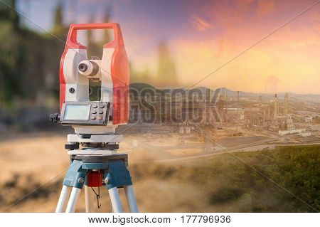 Double exposure surveyor equipment theodolite outdoors with panorama view of oil and gas refinery plant of petroleum or petrochemical industry production construction engineering work concept