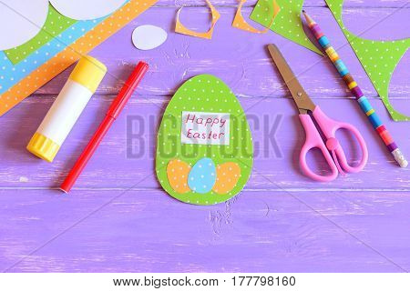Happy Easter greeting card in egg shape. Decorative card made from paper for Easter. Materials and tools for children's art creativity. Easter paper crafts concept for kids
