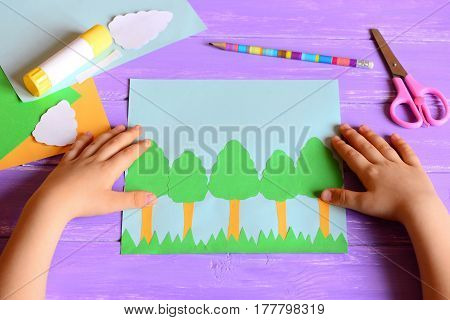 Small child made a Earth day card. Materials and tools for create a simple kids crafts. Children's hands on a desktop. Earth day paper card idea for kids. Learning activities in kindergarten, at home