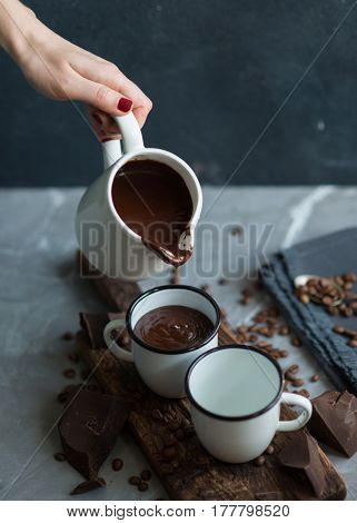 Hot chocolate pouring from milk jug into white enamel mug. Delicious dessert