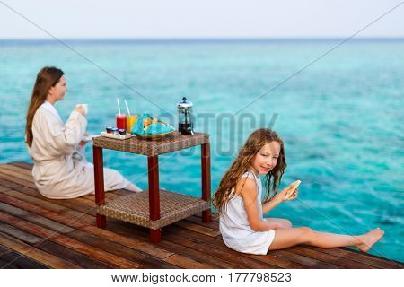 Mother and daughter sitting at wooden dock enjoying ocean view while having breakfast at overwater villa