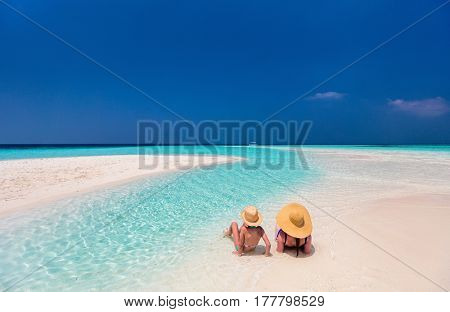 Mother and daughter enjoying tropical beach vacation
