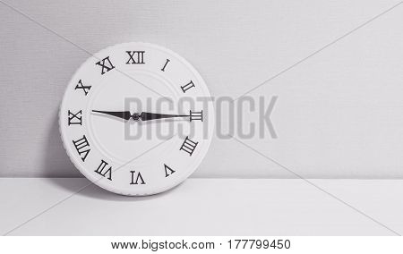 Closeup white clock for decorate show a quarter past nine or 9:15 a.m. on white wood desk and wallpaper textured background in black and white tone with copy space
