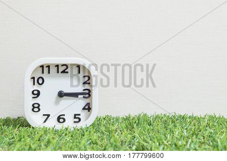 Closeup white clock for decorate show a quarter past three o'clock or 3:15 p.m. on green artificial grass floor and cream wallpaper textured background with copy space