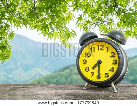 Closeup black and yellow alarm clock for decorate show half past seven or 7:30 a.m. on blurred leaves and mountain view background