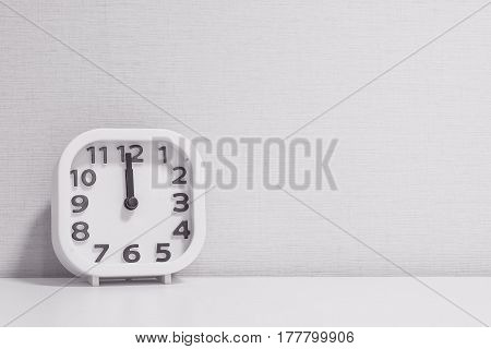 Closeup white clock for decorate in 12 o'clock on white wood desk and cream wallpaper textured background in black and white tone with copy space