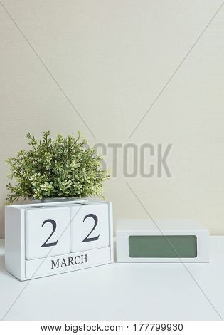 White wooden calendar with black 22 march word with clock and plant on white wood desk and cream wallpaper textured background in selective focus at the calendar