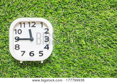 Closeup white clock for decorate show a quarter to twelve o'clock or 11:45 a.m. on green artificial grass floor textured background with copy space