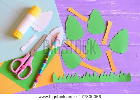 Making Earth day card. Step. Tutorial. Trees and grass cut from colored paper, scissors, glue stick, pencil, template, paper sheets on a wooden table. Earth day paper crafts concept for kids. Top view