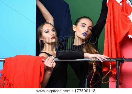 Two pretty girls or sexy women fashion models with long hair stylish makeup red and blue lips in sexi black bodysuits shopping clothes at clothing rack wardrobe on green background