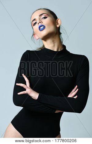 Pretty girl or sexy woman slim fashion model with adorable face blue lips stylish makeup long hair ponytail in sexi black bodysuit on grey background